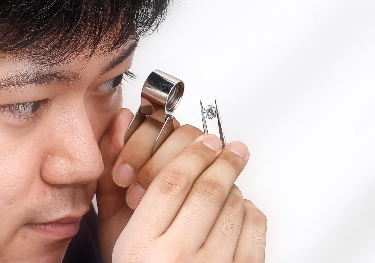 厳選するメレーダイヤモンドのステップ3。10倍ルーペで1点毎に内包物の有無を検査しているシーン