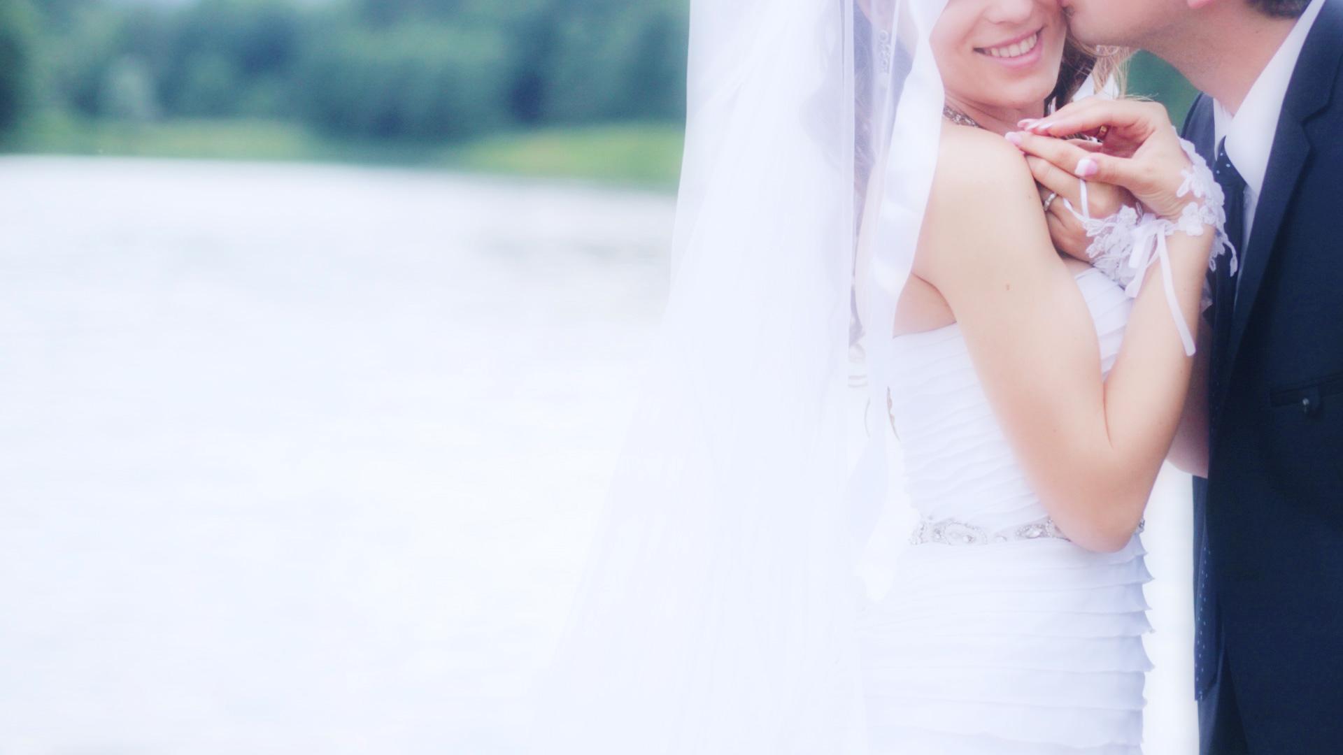 ブライダルのイメージ写真。ウエディングドレスの新婦が湖をバックに新郎と手をつなぎ頬にキスされ幸せを感じる美しいシーン