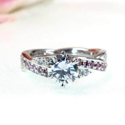 ピンクダイヤモンドと透明なメレーダイヤモンドとクロスするデザインのダイヤモンドリング。